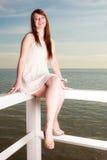 Vrouw in witte korte kledingszitting op hindernis Royalty-vrije Stock Afbeelding