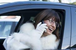 Vrouw in witte laag op telefoon het glimlachen Stock Foto's