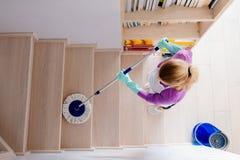 Vrouw in witte schort schoonmakende treden stock foto