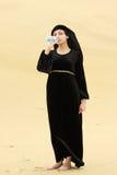 Vrouw in woestijn drinkwater van fles Royalty-vrije Stock Afbeelding