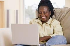Vrouw in woonkamer die laptop met behulp van Royalty-vrije Stock Foto's