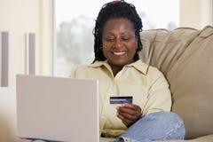 Vrouw in woonkamer die laptop met behulp van Stock Foto's