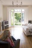 Vrouw in woonkamer die op telefoon spreekt Stock Afbeelding