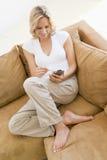 Vrouw in woonkamer die PDA gebruikt Stock Afbeelding