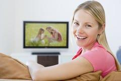Vrouw in woonkamer het letten op televisie royalty-vrije stock fotografie