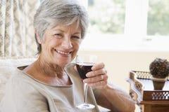 Vrouw in woonkamer met glas van wijn het glimlachen royalty-vrije stock afbeelding