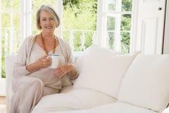 Vrouw in woonkamer met koffie het glimlachen Stock Foto's