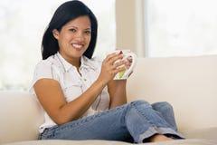 Vrouw in woonkamer met koffie het glimlachen Royalty-vrije Stock Afbeeldingen