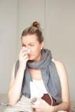 Vrouw ziek in bed dat haar neus blaast Royalty-vrije Stock Afbeelding