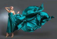 Vrouw in zijdekleding die op wind golven Vliegende en fladderende togadoek over grijze achtergrond Stock Foto's