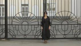 Vrouw in zonnebril dichtbij poort stock footage