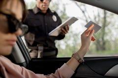 vrouw in zonnebril die in auto zitten en bestuurdersvergunning geven aan stock afbeelding