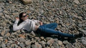 Vrouw in zonnebril die op een steenstrand in de herfst liggen Steen op de buik van het meisje stock video
