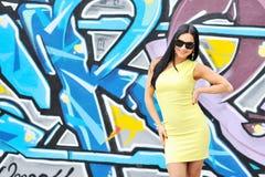 Vrouw in zonnebril die tegen graffitymuur stellen Stock Afbeelding