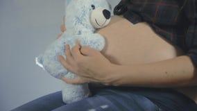 Vrouw zwanger met jong geitjeholding teddybear dicht bij buik het spelen stock video