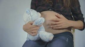 Vrouw zwanger met jong geitjeholding teddybear dicht bij buik het spelen stock footage