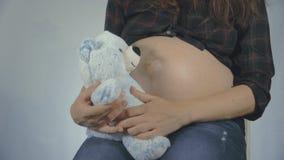 Vrouw zwanger met jong geitjeholding teddybear dicht bij buik het spelen stock videobeelden