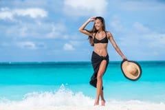 Vrouw in zwarte bikini en sarongen die op strand lopen Royalty-vrije Stock Fotografie