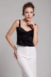 Vrouw in zwarte blouse en witte broeken Royalty-vrije Stock Fotografie