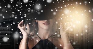 Vrouw in zwarte hoed over stadsachtergrond en sneeuw royalty-vrije stock fotografie