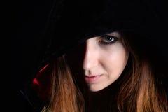 Vrouw in zwarte kap stock foto