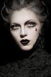 Vrouw in zwarte kleren met expressieve donkere make-up stock afbeelding