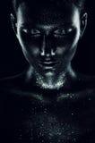 Vrouw in zwarte verf met fonkelingen in dark royalty-vrije stock fotografie