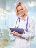 Vrouwelijk artsenklembord en het schrijven daarin Royalty-vrije Stock Afbeeldingen