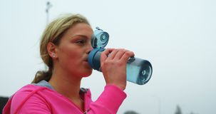 Vrouwelijk atleten drinkwater bij sportentrefpunt 4k stock video