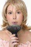 Vrouwelijk blazend bovenmatig poeder van make-upborstel Royalty-vrije Stock Fotografie
