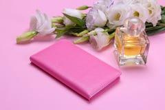 vrouwelijk blocnote en parfum naast de bloemen van eustoma op een heldere roze achtergrond stock fotografie
