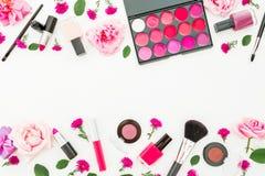 Vrouwelijk bureau met vrouwen kosmetische en roze rozen op witte achtergrond Vlak leg, hoogste mening Het kader van de schoonheid Royalty-vrije Stock Afbeeldingen