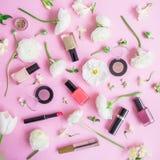 Vrouwelijk bureau met vrouwenschoonheidsmiddelen en witte bloemen op roze achtergrond Vlak leg, hoogste mening Schoonheidsconcept Stock Afbeelding