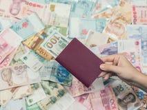 Vrouwelijk de reispaspoort van de handholding met honderd Amerikaanse dollars binnen op de achtergrond van de het geldtextuur van Stock Afbeeldingen