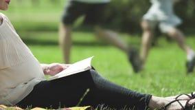 Vrouwelijk denkend kind die in park rusten en boek over zorg van pasgeboren lezen stock videobeelden