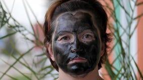 Vrouwelijk die gezicht met een zwart masker wordt behandeld stock footage