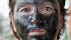 Vrouwelijk die gezicht met een zwart masker wordt behandeld stock video