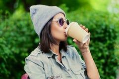 Vrouwelijk drinkt koffie in een de zomerpark Stock Foto