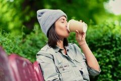 Vrouwelijk drinkt koffie in een de zomerpark Royalty-vrije Stock Afbeelding