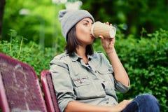 Vrouwelijk drinkt koffie in een de zomerpark Royalty-vrije Stock Afbeeldingen