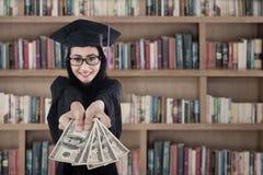 Vrouwelijk gediplomeerd holdingsgeld bij bibliotheek Stock Afbeeldingen