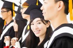 vrouwelijk gegradueerde bij graduatie met klasgenoten stock afbeeldingen