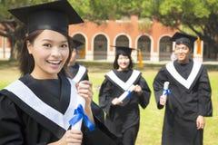 Vrouwelijk gegradueerde met klasgenoten en holding een diploma stock afbeeldingen