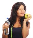 Vrouwelijk geschiktheidsmodel die een waterfles en een groene appel houden Stock Foto
