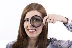 Vrouwelijk gezicht die door meer magnifier kijken Stock Foto's