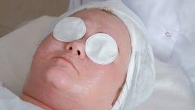 Vrouwelijk gezicht met katoenen stootkussens op de ogen Het verjongen van procedure in de schoonheidssalon Massage, het schoonmak stock afbeelding
