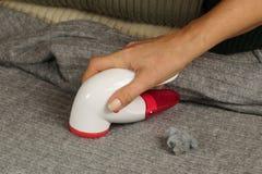 Vrouwelijk hand en apparaat om het pilling te verwijderen Het verwijderen van pluksel het pilling uit de sweater royalty-vrije stock afbeeldingen