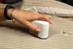 Vrouwelijk hand en apparaat om het pilling te verwijderen Het verwijderen van pluksel het pilling uit de sweater royalty-vrije stock afbeelding