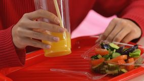 Vrouwelijk het drinken jus d'orange van plastic kop, die op plantaardige salade, dieet snacking stock video