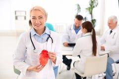 Vrouwelijk het hartmodel van de artsenholding in kliniek Stock Afbeeldingen